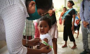 In Covalima, nurses use a colour-coded tag to measure children's middle upper arm circumference and see if it is thick enough for their age.