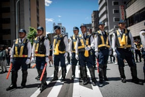 Japanese policemen stand guard during the Sanja Matsuri festival