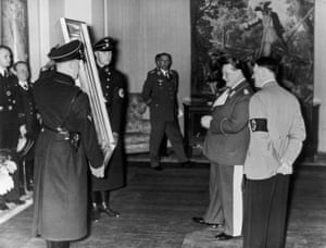 German Field-Marshal Hermann Goering (second from right) admires a painting given to him by Adolf Hitler (right) for his 45th birthday.