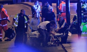 Police officers and members of the emergency services attend to a person injured on London Bridge.