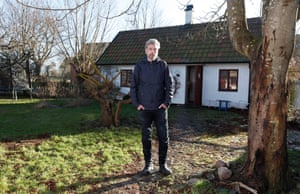 karl ove knausgaard standing on a bright early spring day outside a cottage