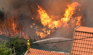 A firefighter stands on the roof of a house and tries to extinguish a wildfire at Curral dos Romeiros.