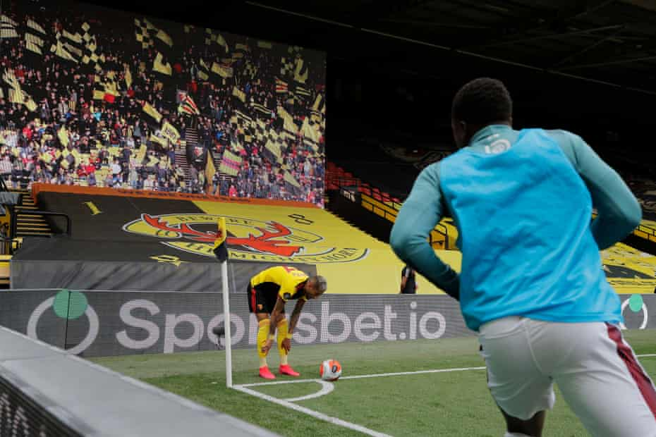 Roberto Pereyra prepares to take a corner in front of a temporary screen displaying Watford fans.
