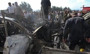叙利亚安全部队,紧急服务部门和居民在塔尔图斯的一次爆炸现场查看被烧毁车辆的残骸。
