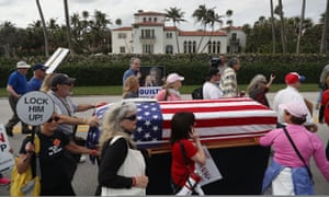 People push a coffin though the streets to represent the end of democracy as they protest against Donald Trump in Palm Beach, Florida.