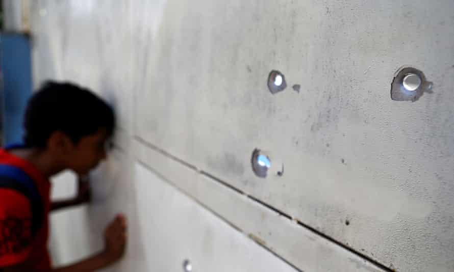 A boy peers through bullet holes after a gunfight outside a a supermarket in one of Caracas's poorer neighbourhoods.