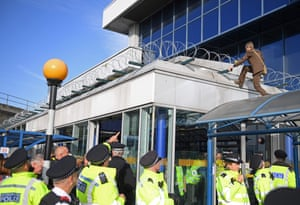 London, England An activist, dressed in a suit, scales the roof above the entrance to London City airport during the fourth day of demonstrations by the climate change action group Extinction Rebellion
