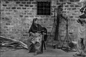 Nawab Khan (right), a community activist who works with survivors of the Union Carbide factory disaster, arrives at the home of an elderly widow to see if she needs any help in making her next doctor's appointment. Her husband died of complications from exposure to the toxic gas cloud released by the explosion at the factory. She makes a living from selling fire wood.