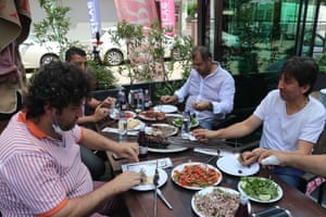 Men eat at a restaurant in Adana on Monday.