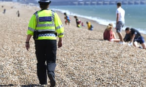 Police community support officer patrols the beach in Brighton