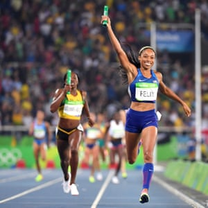 The USA's Allyson Felix holds her baton up as she crosses the finish line to win the women's 4x400m elay final.