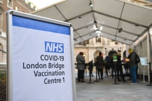 People queue at an NHS Covid-19 vaccination centre in London as cases of the virus continue to soar and the Government raises restrictions around the country.