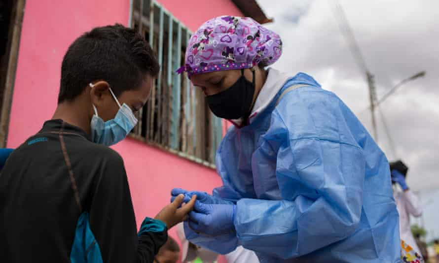 A medical volunteer of the Doctors Without Borders (MSF) organization takes a blood sample from a patient to be tested for malaria at his home in Barcelona, Anzoategui State, Venezuela, on 16 March 2021.
