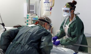 Nurses care for a patient in an Intensive Care ward treating victims of the coronavirus disease.