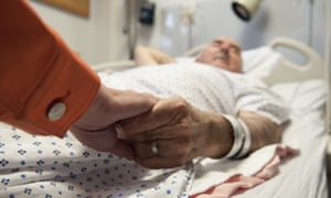 Elderly man in hospital bed, holding someone's hand