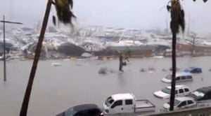 Half-submerged vehicles, boats and debris in the flooded harbour of Saint Martin.