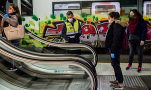 A security guard controls the distance between commuters on escalators at Catalunya station in Barcelona.