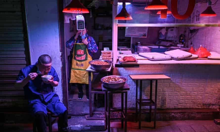 A man eats in a market in Wuhan