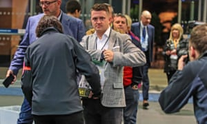 Tommy Robinson goes through a security check on arrival for the election count in Manchester