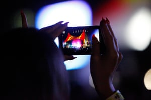 A fan snaps a photo of the performance on her camera-phone.