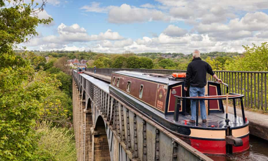 Man with his hand on the tiller, steering narrowboat over the Pontcysyllte Aqueduct