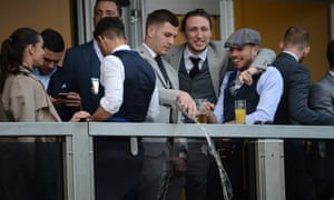 Samir Carruthers in the flat cap, right, laughs as the Northampton Town forward James Collins empties the contents of a glass over the balcony.