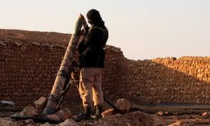 An image taken from Isis propaganda footage shows a jihadi fighter on patrol in Raqqa, Syria.