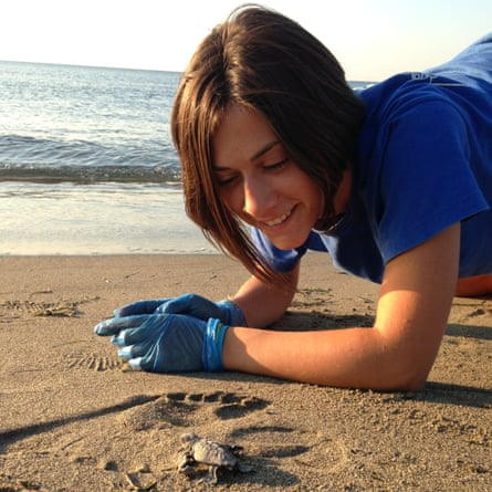 Volunteer with turtle hatchling on a beACH Greece