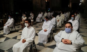 Acolytes wear protective face masks as they attend a funeral mass for the coronavirus victims at the cathedral in Seville.