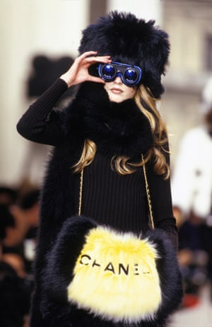Chanel Autumn/Winter 94/95 show: a model with binoculars wears a fur coat, a fur bag and a fur hat – a look that would spark considerable controversy among animal rights activists today