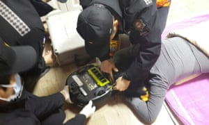 Firefighters try to rescue a woman at her house in Changwon, southeast South Korea after her hair was sucked into a robot vacuum cleaner. She lost about 10 strands of hair but was not injured.