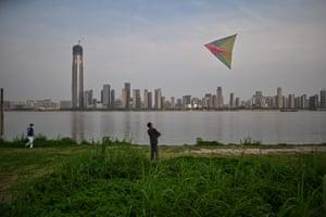 Wuhan, China A man flies a kite by the Yangtze river