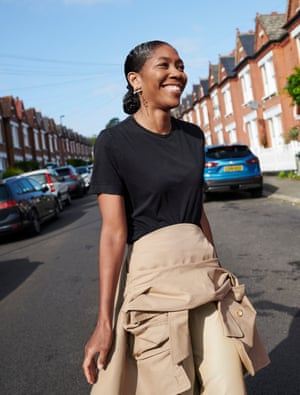 Kenya Hunt in a black T-shirt and with a coat tied around her waist, walking across a road with a row of houses behind her