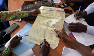 Congolese officials tally the presidential ballots at a local results compilation centre in Kinshasa, Congo.