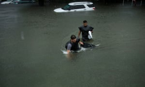 People wade through flooded streets in the aftermath of the hurricane.