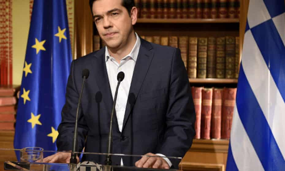 Tsipras at a podium with Greek and Euro flags