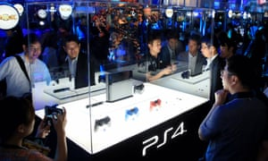 Visitors and media reporters ogle a PS4 game console during the Tokyo Game Show in 2013.