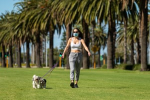 A masked dog walker is seen in Perth on Sunday. Masks have become mandatory after a security guard in his 20s who worked at the Pan Pacific Hotel between 24 and 26 April tested positive for Covid.