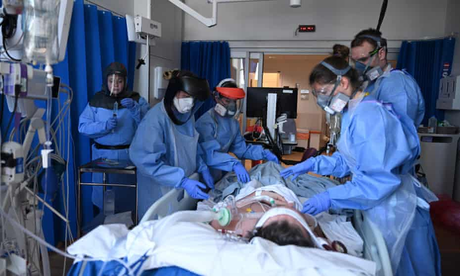 Clinical staff wearing PPE as they care for a patient at the intensive care unit at Royal Papworth hospital in Cambridge.