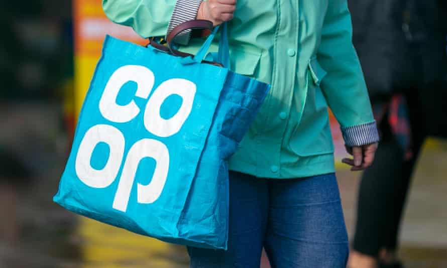 a woman carries the signature Co-op shopper bag
