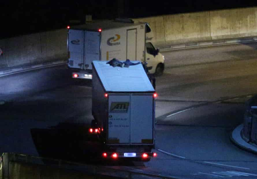 Two migrants cling to the roof of a freight truck as it leaves the Eurotunnel terminal on Friday