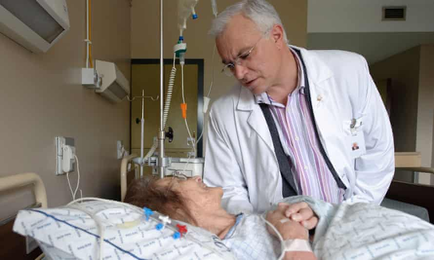 Male doctor tending to elderly female patient on a drip in a hospital bed