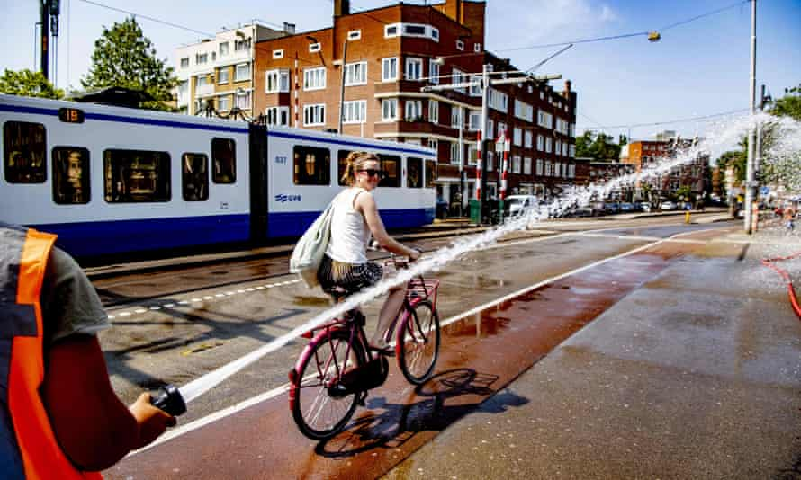 A firefighter sprays water as a woman rides her bicycle during the recent heatwave in Amsterdam.