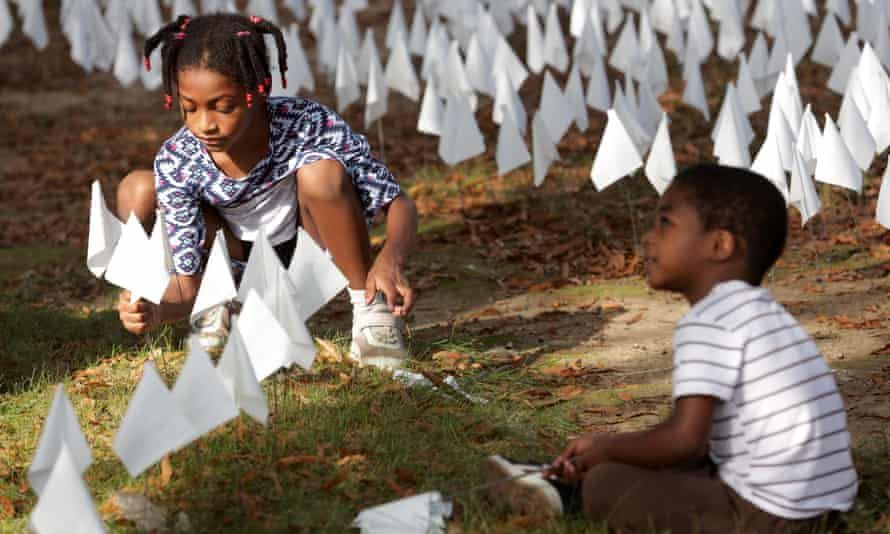 Hope Larkin plants flags with her brother Walter Larkin during a press preview of the public art project 'IN AMERICA How could this happen …' on the DC Armory Parade Ground in Washington DC.