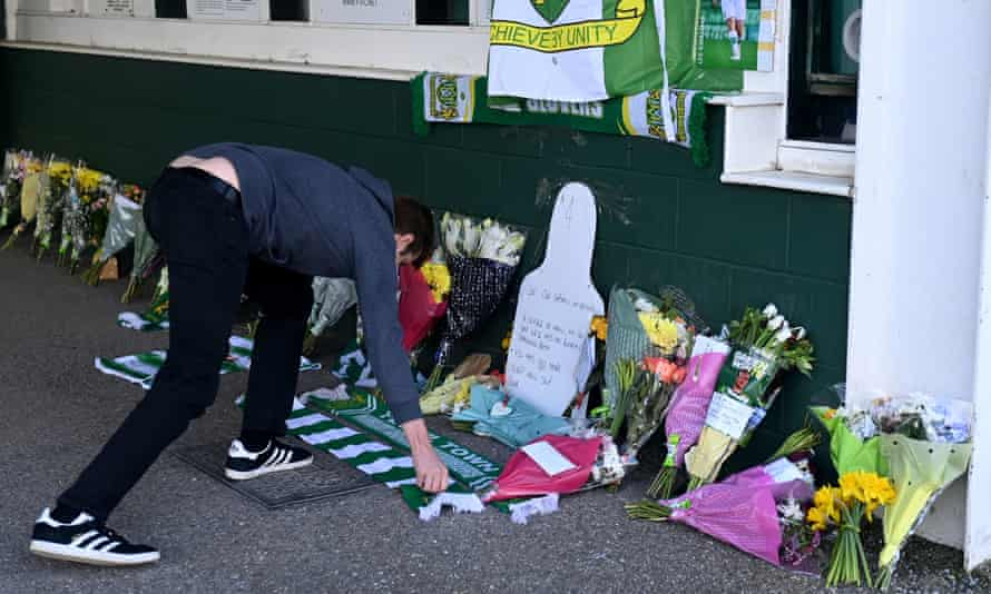 A fan leaves his scarf among tributes to Lee Collins, who died at the age of 32 in March.