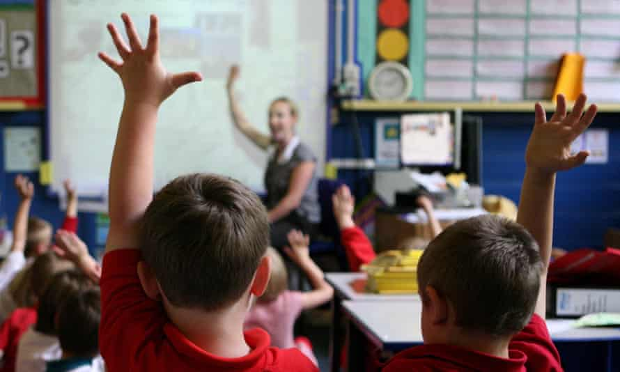 eager children putting up their hands in class