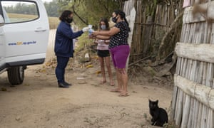 A school worker drops off schoolwork for Giovana, 9, and a bag of hygiene products to her mother Amanda Trindade in the rural area of Sao Jose dos Campos, Brazil, 14 July 2020.