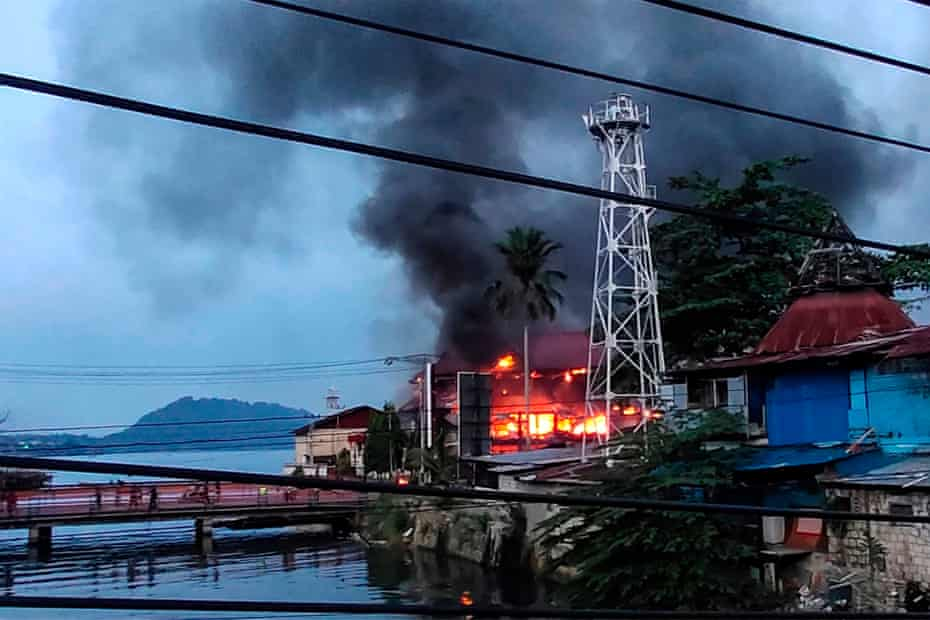 Smoke billows from a building after hundreds of demonstrators marched near Papua's biggest city Jayapura.