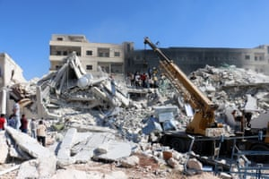 Rescue teams search the wreckage of the two buildings destroyed in Sarmada.