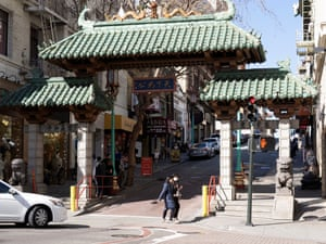 People wear protective masks while crossing the street at the entrance to a largely deserted Chinatown in San Francisco on Wednesday.
